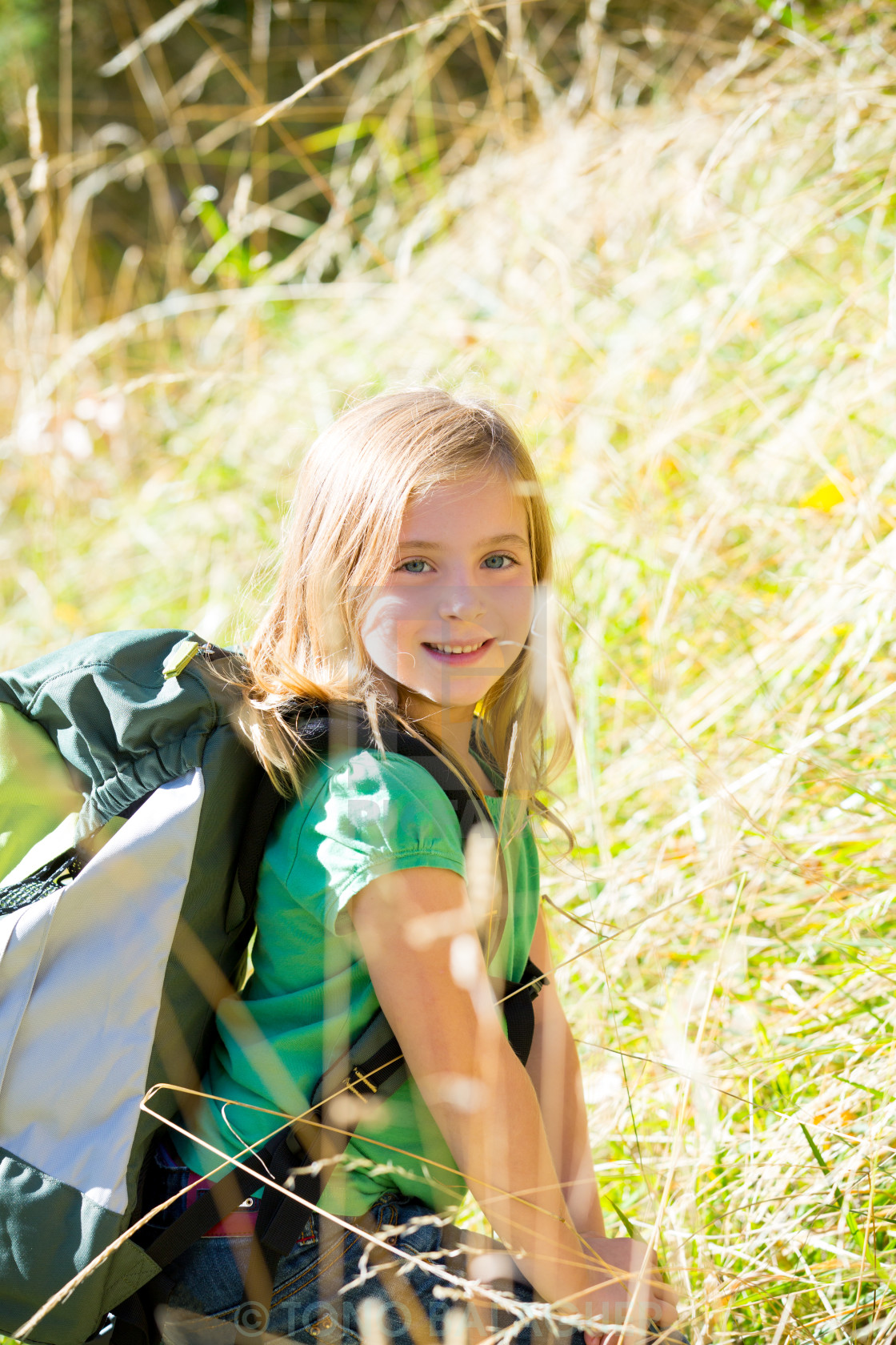 """""""Blond explorer kid girl walking with backpack in grass"""" stock image"""