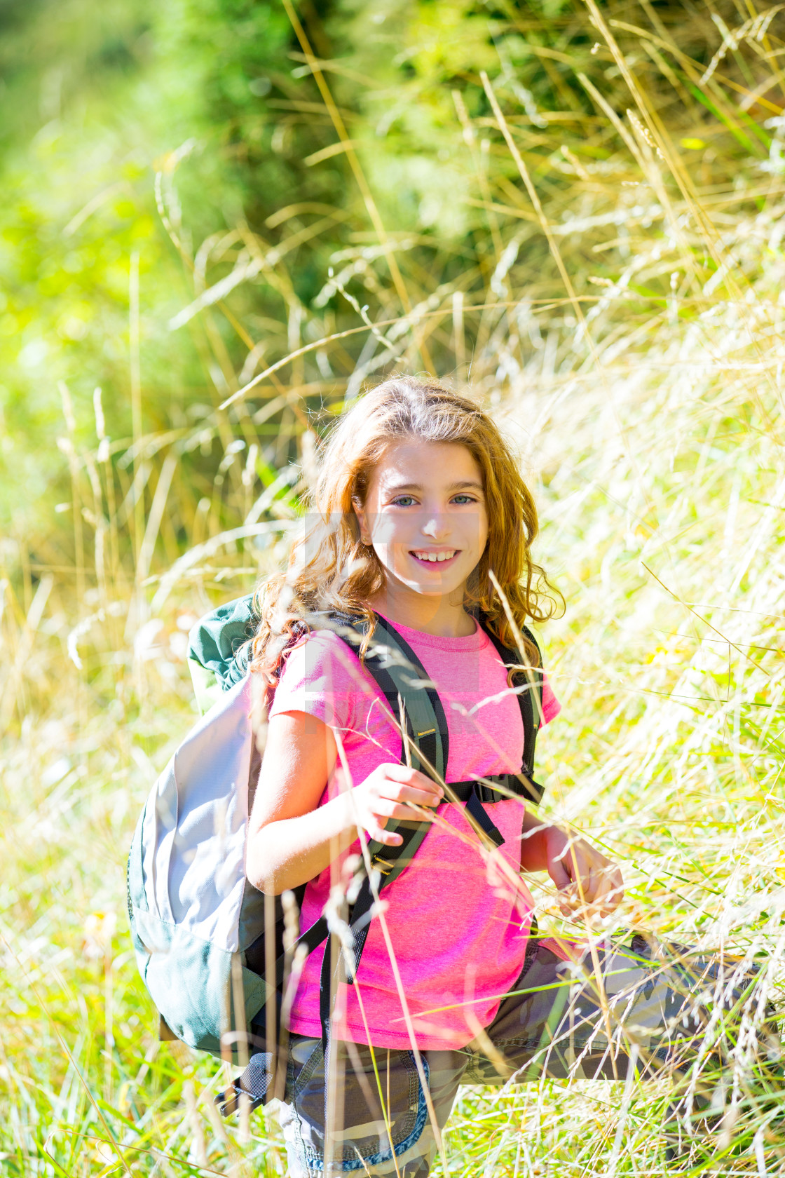 """""""Explorer kid girl walking with backpack in grass"""" stock image"""