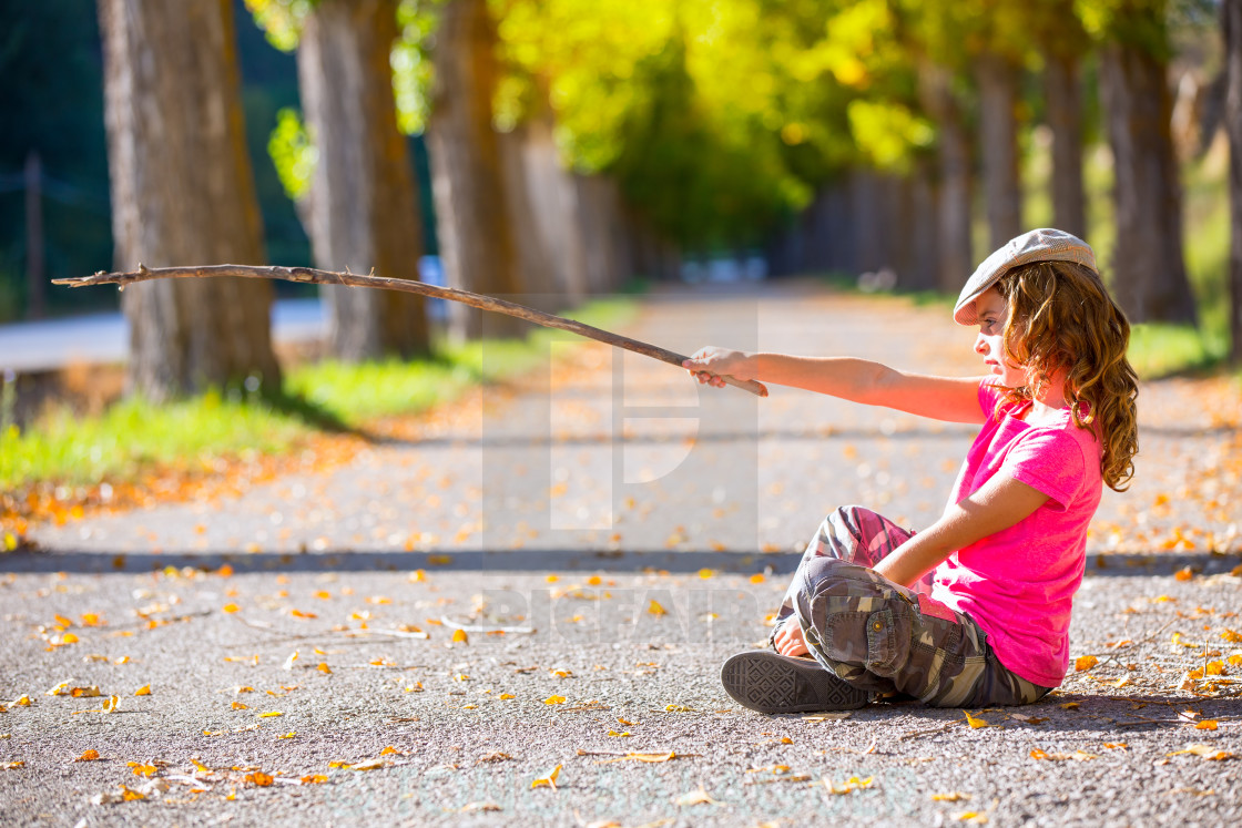 """""""autumn kid girl with camouflage pants sitting in trees track"""" stock image"""
