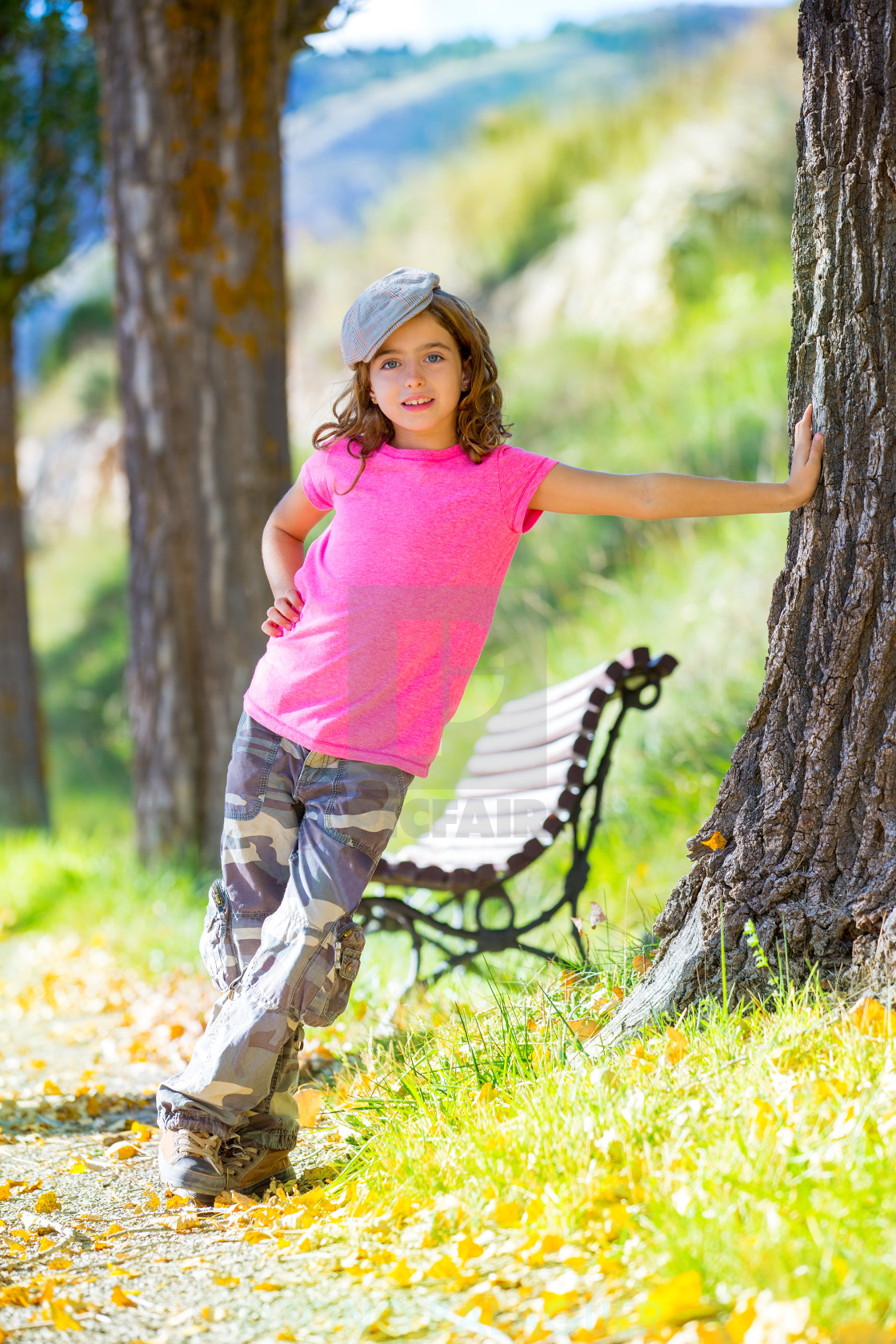"""kid girl with camouflage pants and cap in park bench outdoor"" stock image"