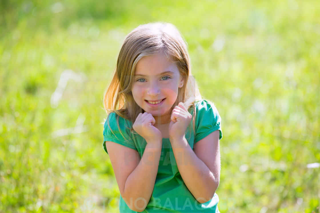"""Blond kid girl excited gesture expression in green outdoor"" stock image"