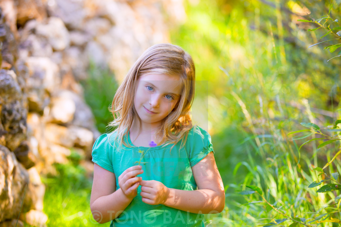 """""""Blond kid girl smiling with purple flower relaxed outdoor"""" stock image"""