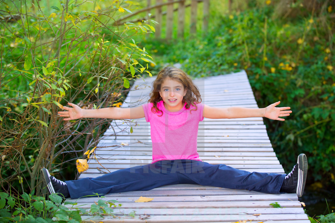 """Kid girl in autumn smiling with braces open arms and legs"" stock image"
