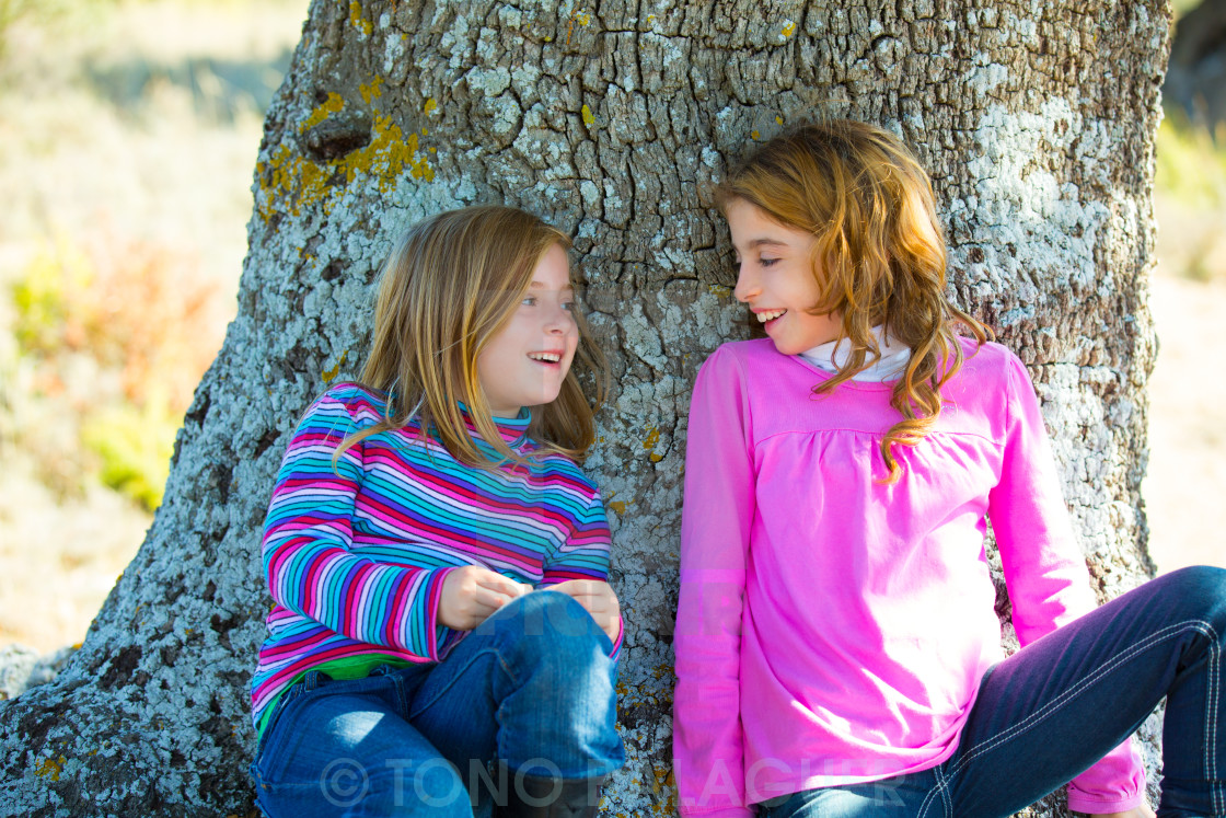 """""""Sister kid girls smiling sit relaxed in a oak tree trunk"""" stock image"""