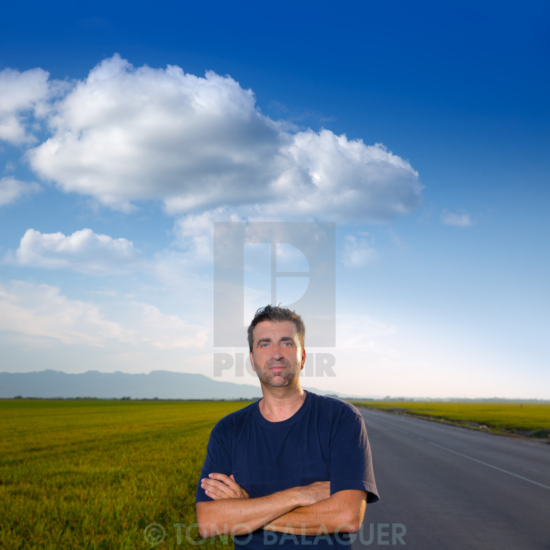 """""""Mid age man in road at meadows posing crossed arms"""" stock image"""