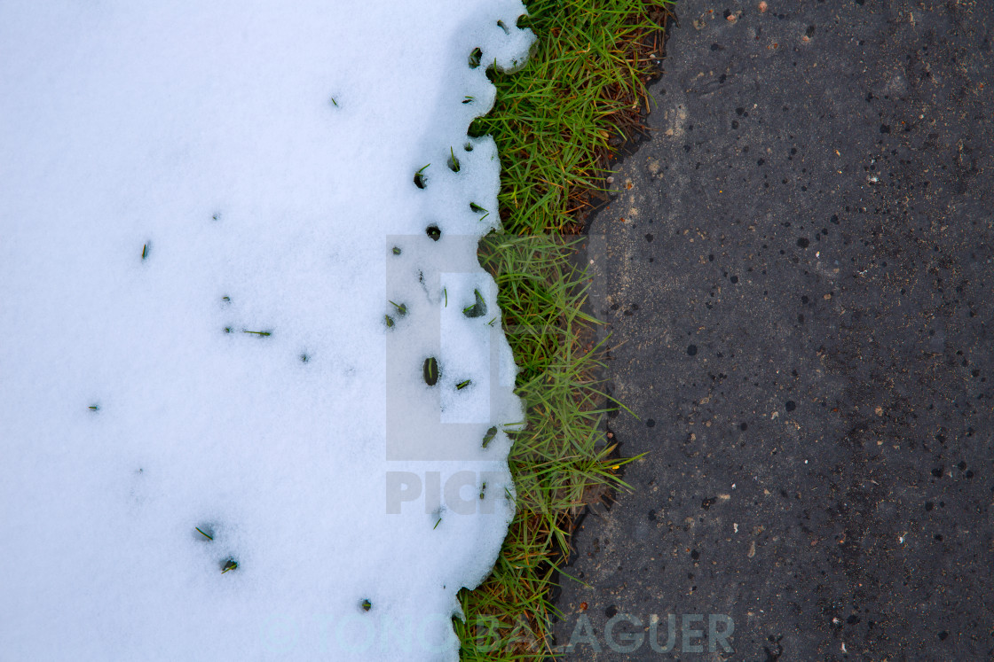"""Snow in road with turf grass line"" stock image"