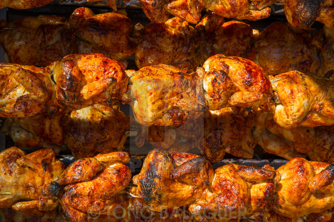 """""""Roasted chicken in a row turning on a roaster"""" stock image"""