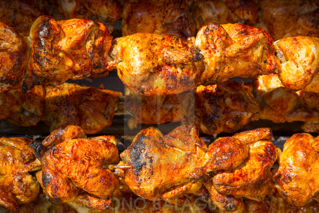 """Roasted chicken in a row turning on a roaster"" stock image"
