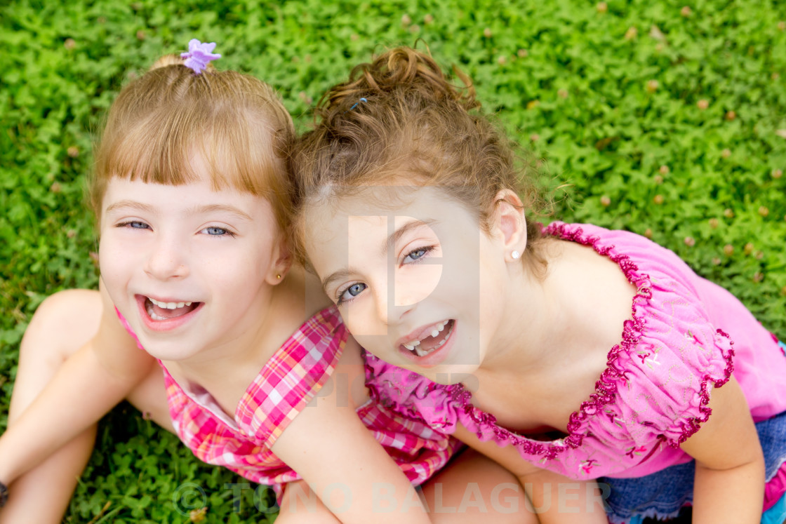 """children girls laughing sit on green grass"" stock image"