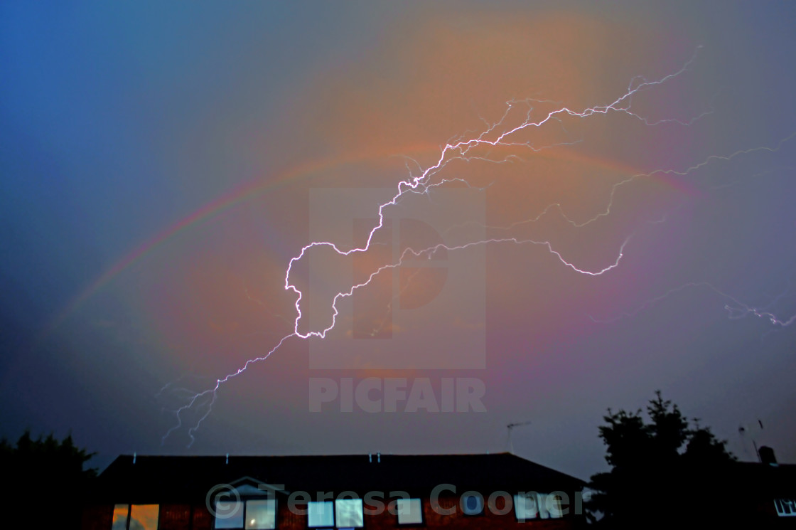 """Lightning strikes through the heart of a rainbow"" stock image"