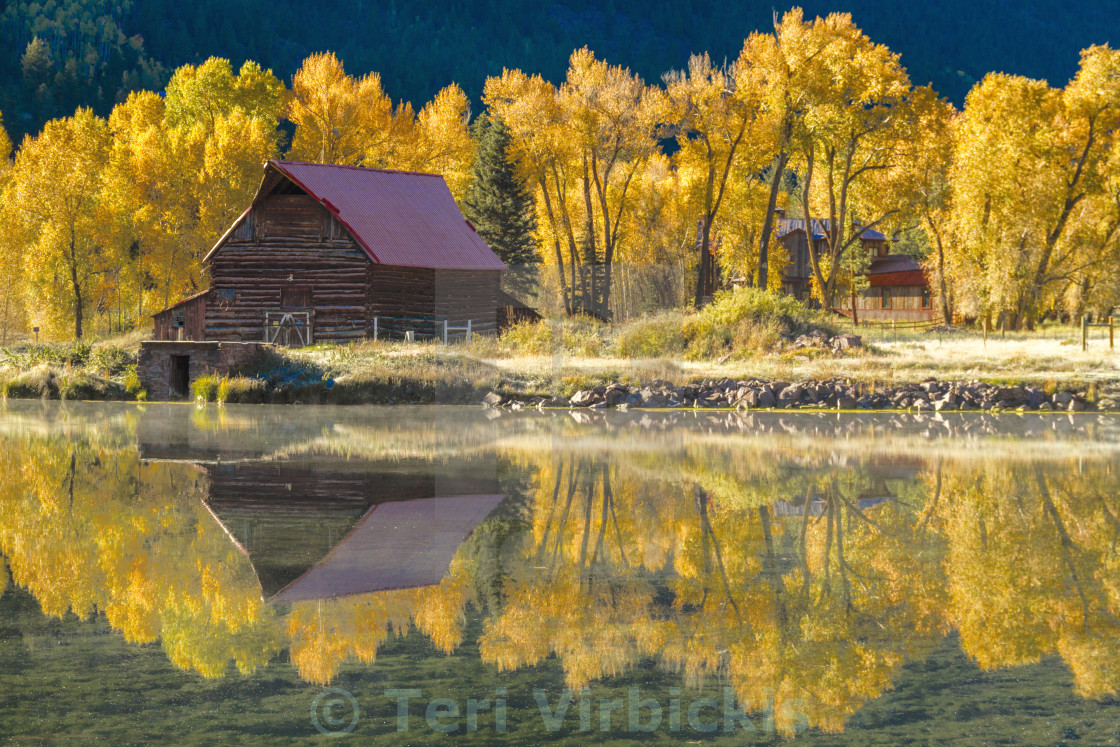 """Barn Reflecting in Lake Surround By Fall Color"" stock image"