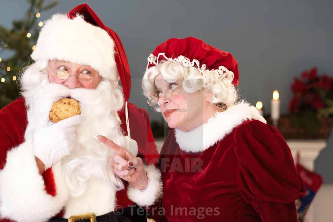 Mrs Claus Pointing On Santa Eating Gingerbread Cookie Stock Image