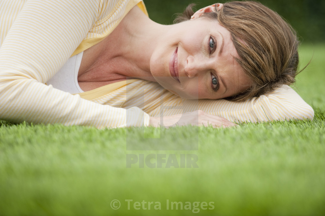 """""""Contented woman lying on grass"""" stock image"""