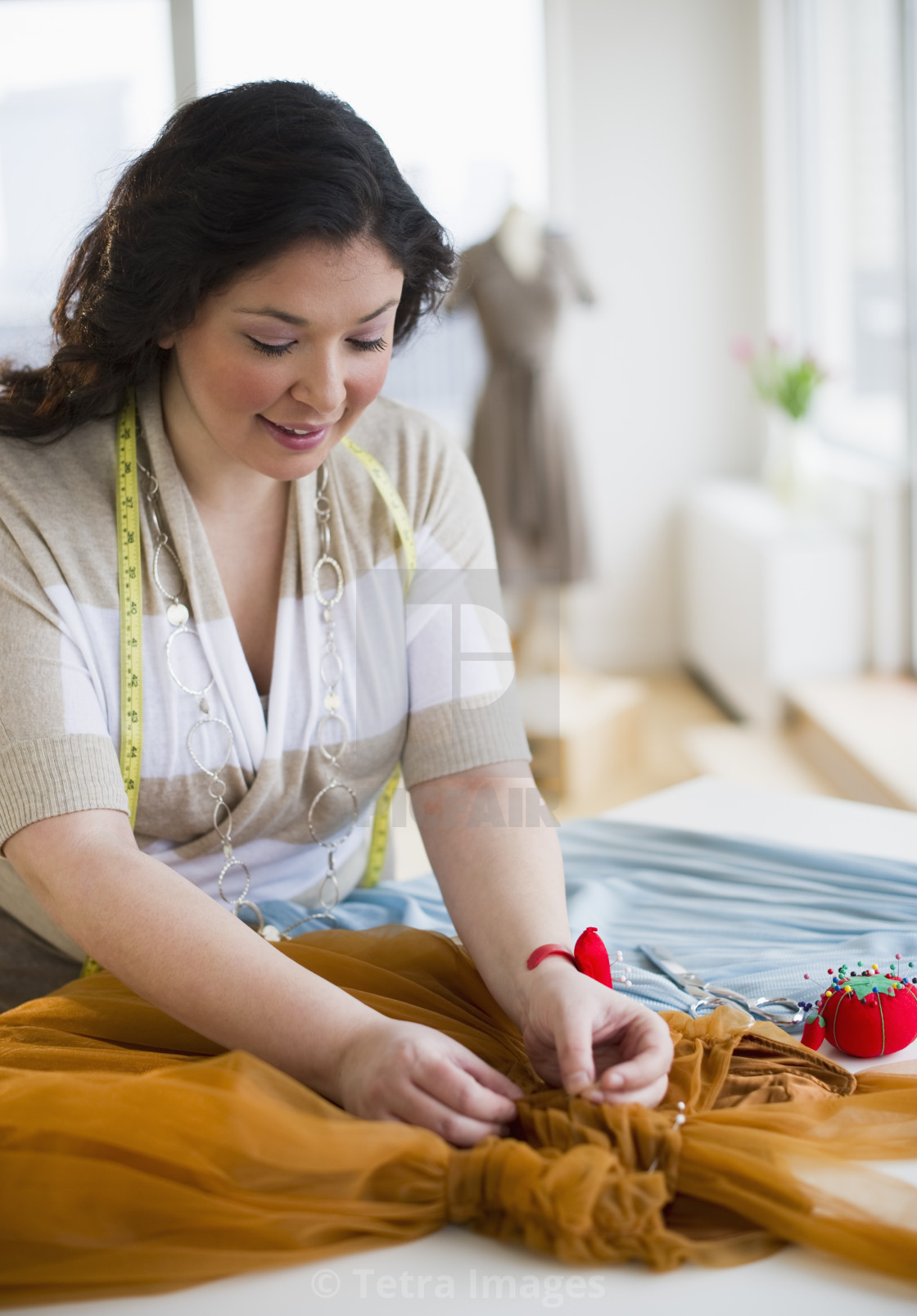 """Tailor mending a dress"" stock image"