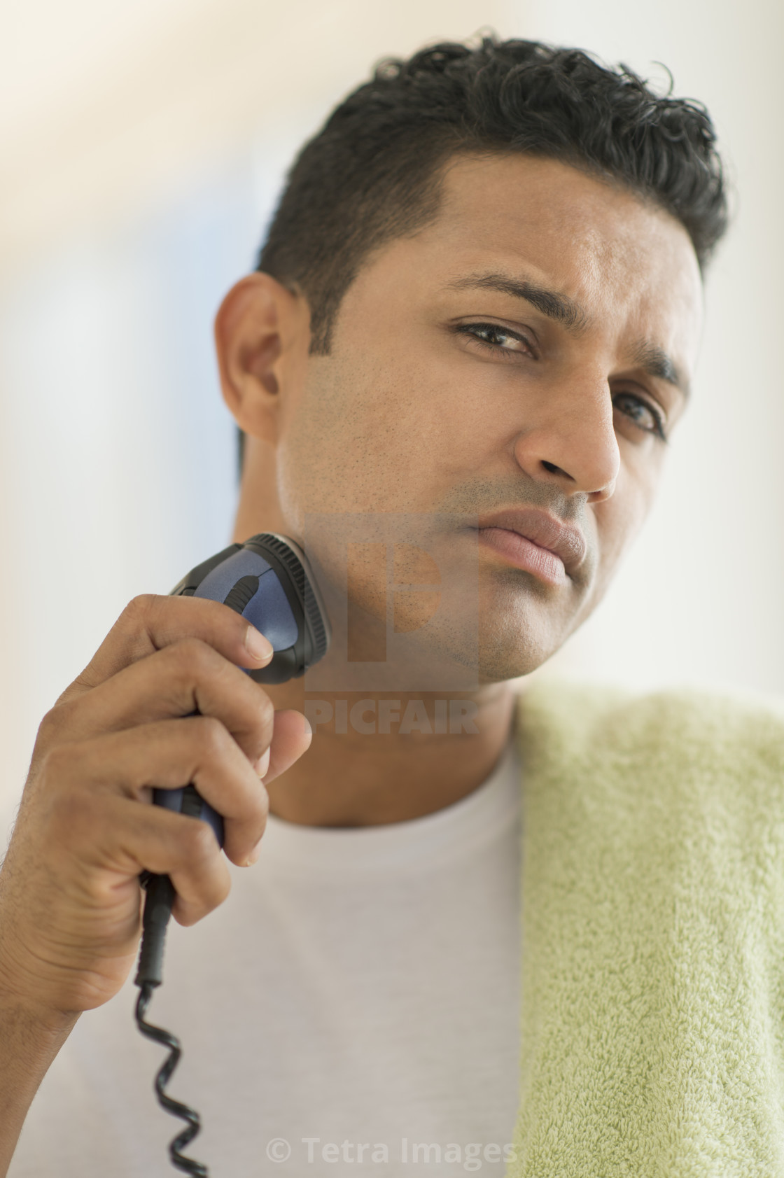"""Man shaving with electric razor"" stock image"