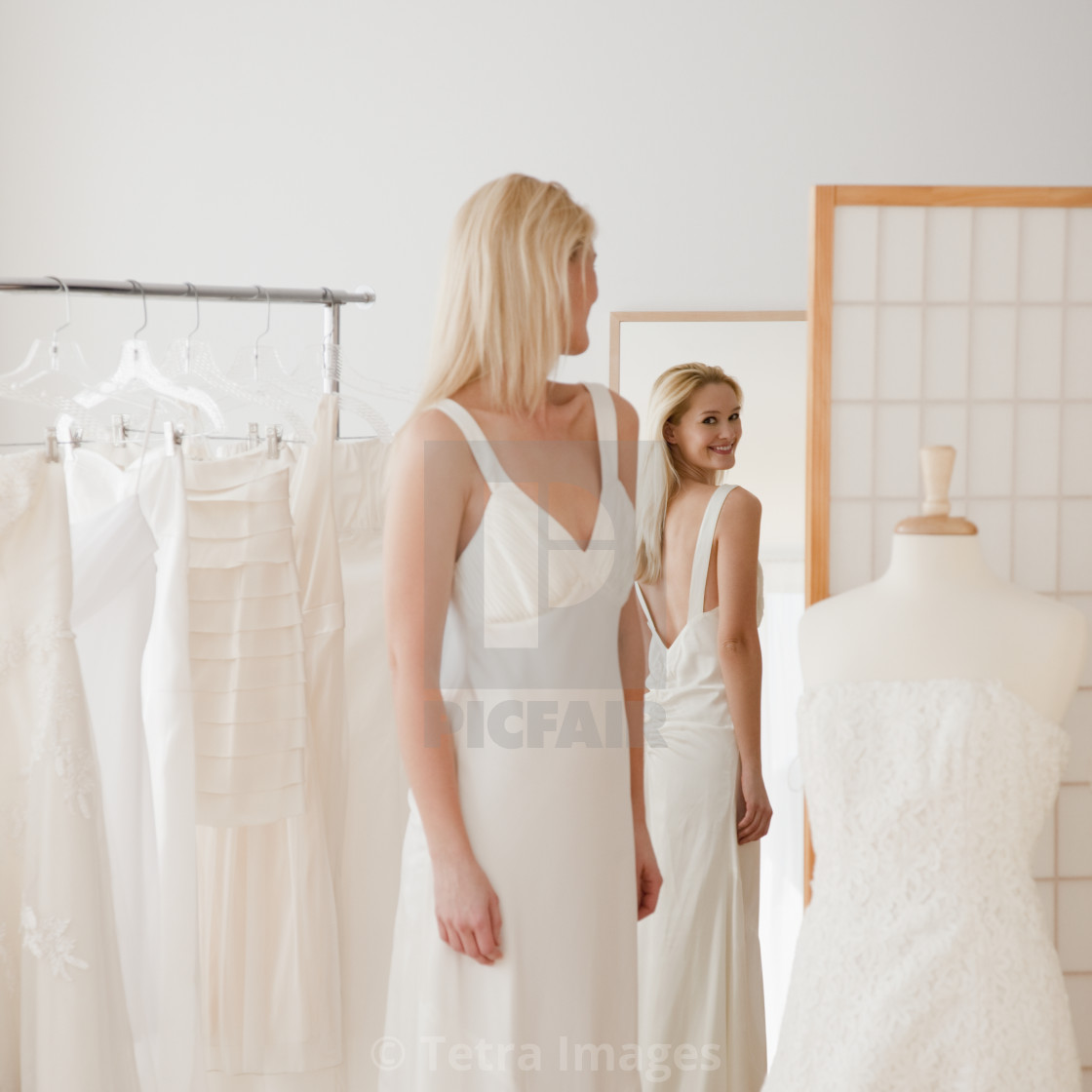 Young Woman Trying On Wedding Dress In Bridal Shop License