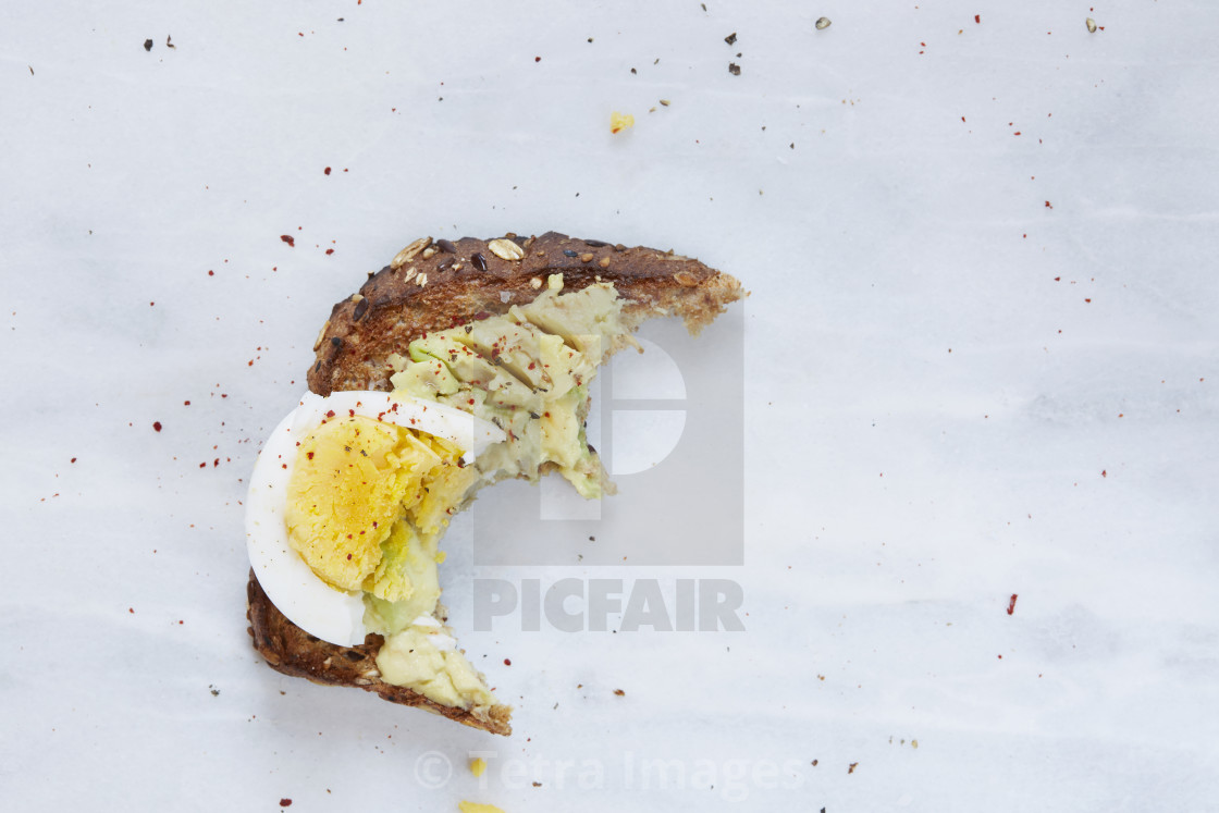 """Missing bite of toasted bread with avocado and hard boiled egg"" stock image"
