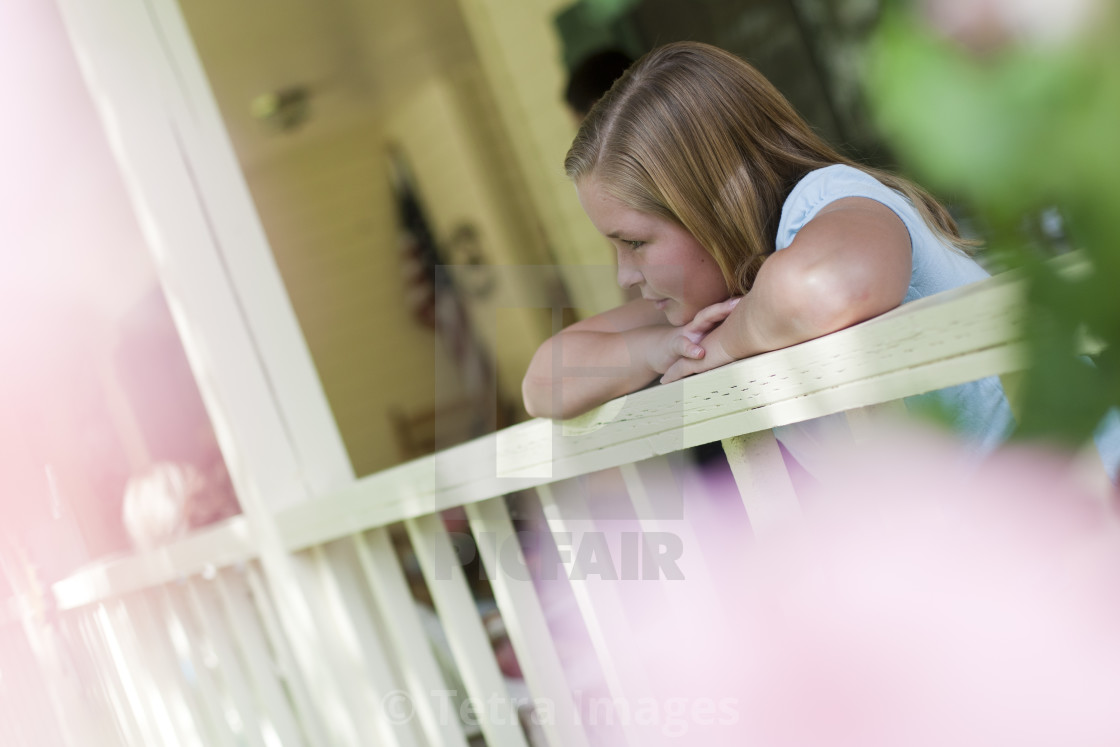 """Young girl gazing over porch railing"" stock image"