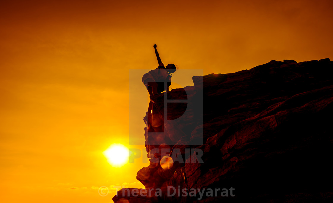 """Silhouette sporty woman on the cliff. Sunset and high mountain. Business Success and goal."" stock image"