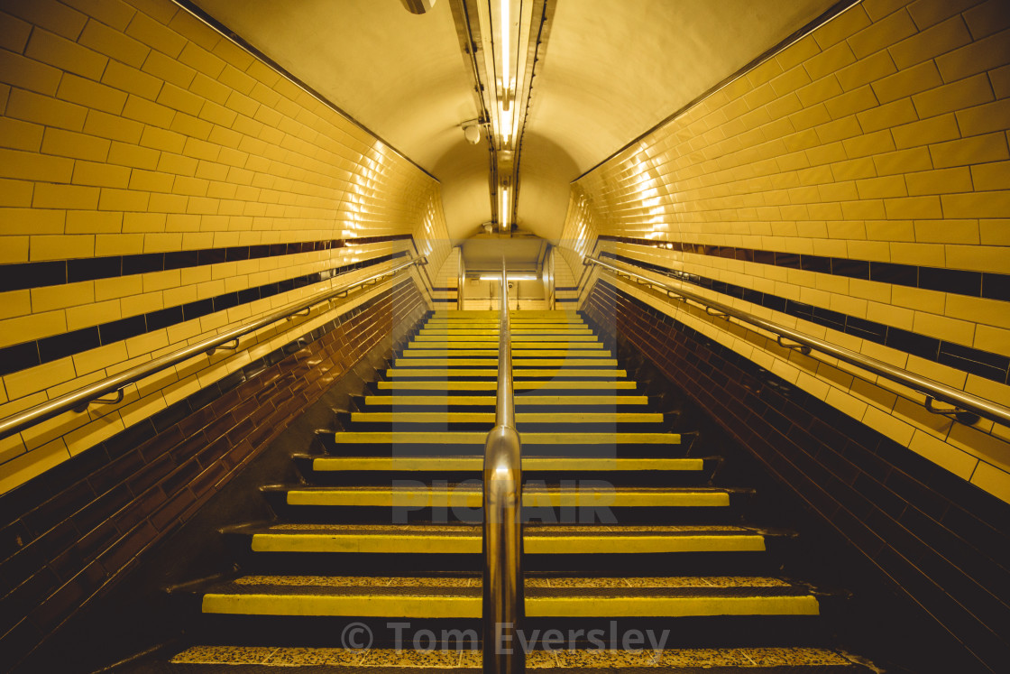 """Moody yellow tunnel and staircase on London underground"" stock image"