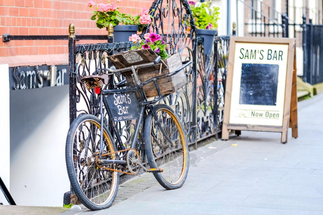 """Bike advertises Sam's Bar."" stock image"