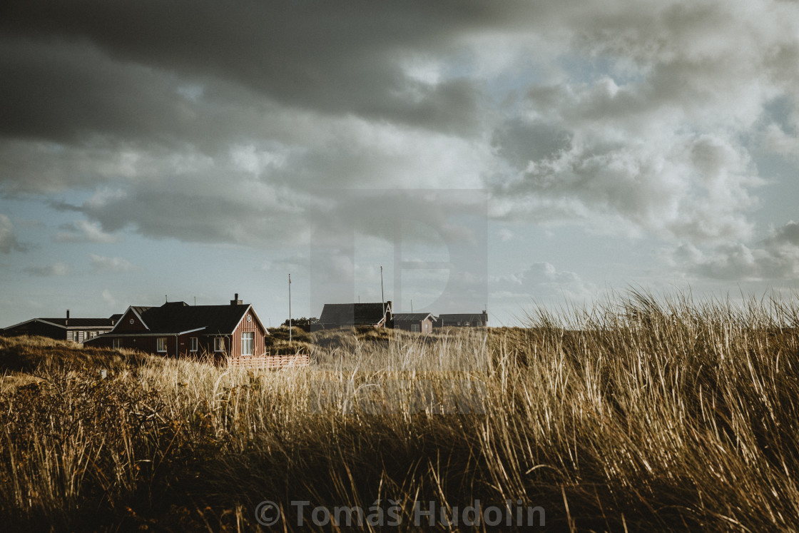 """""""Typical wooden holiday homes of Rømø island in Denmark during the autumn afternoon with the cloudy sky above them"""" stock image"""