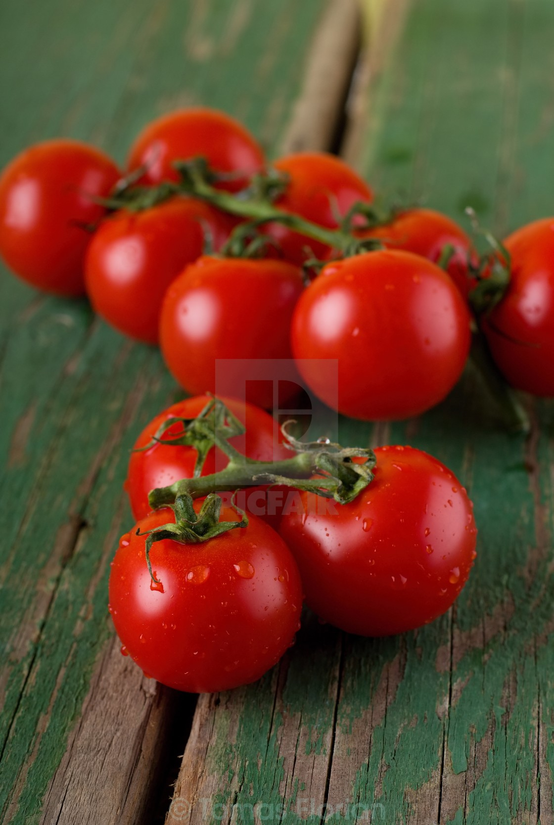"""Juicy cherry tomatoes on green table"" stock image"