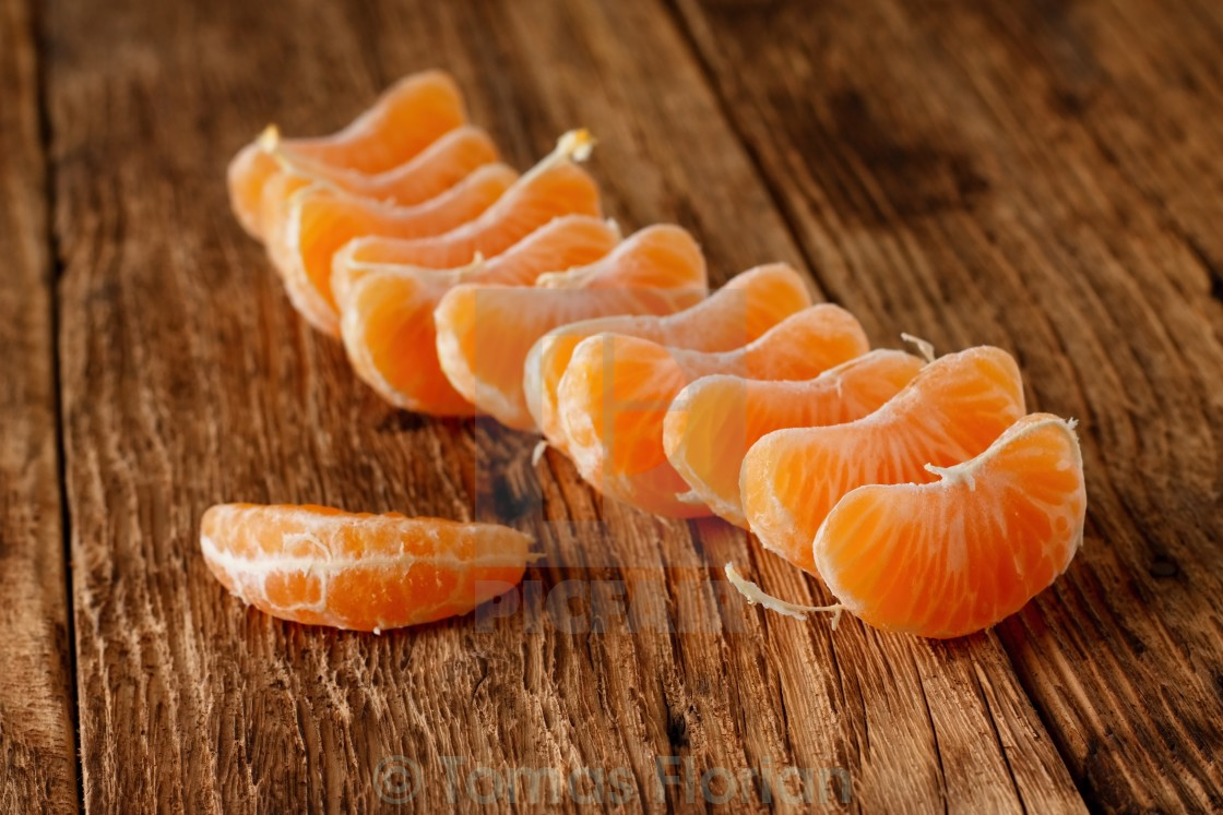 """Pieces of mandarin fruit on wooden board"" stock image"