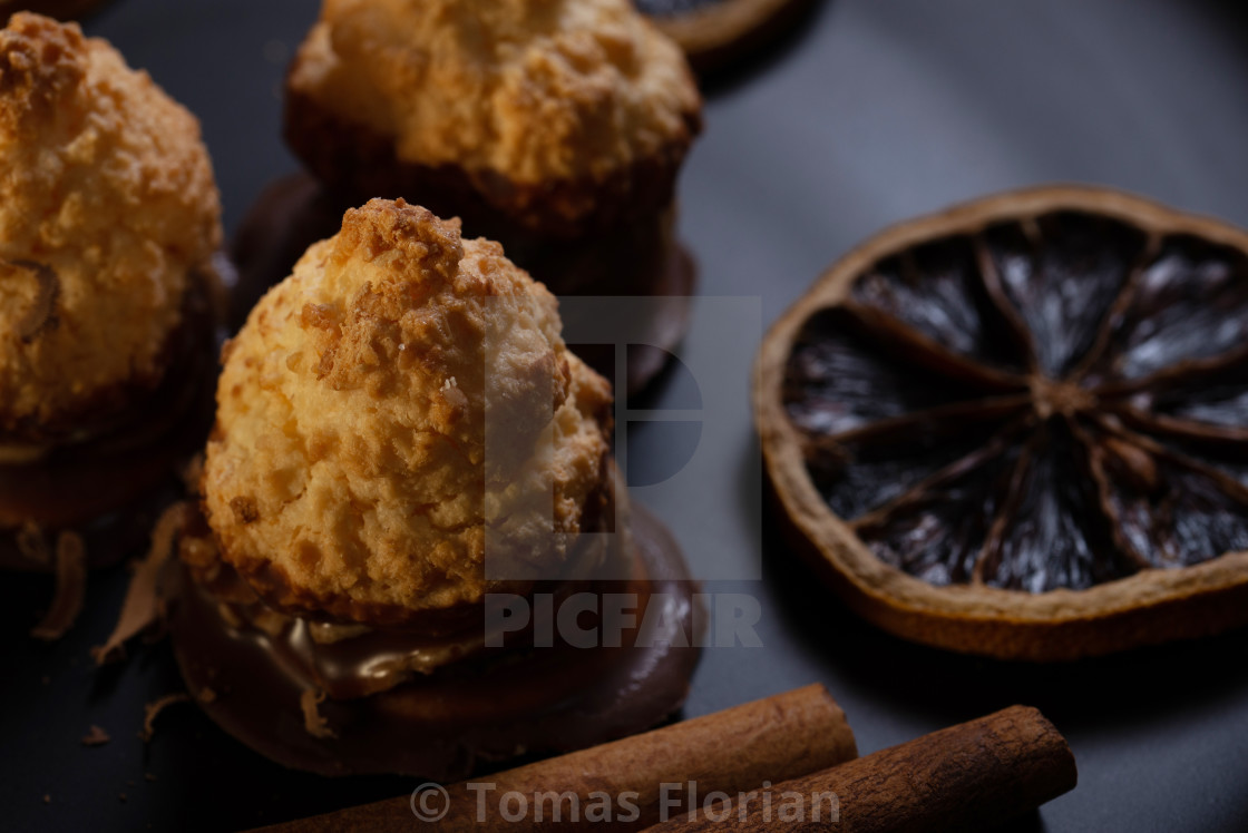 """Few pieces of baked sweets on dark plate with orange rings"" stock image"