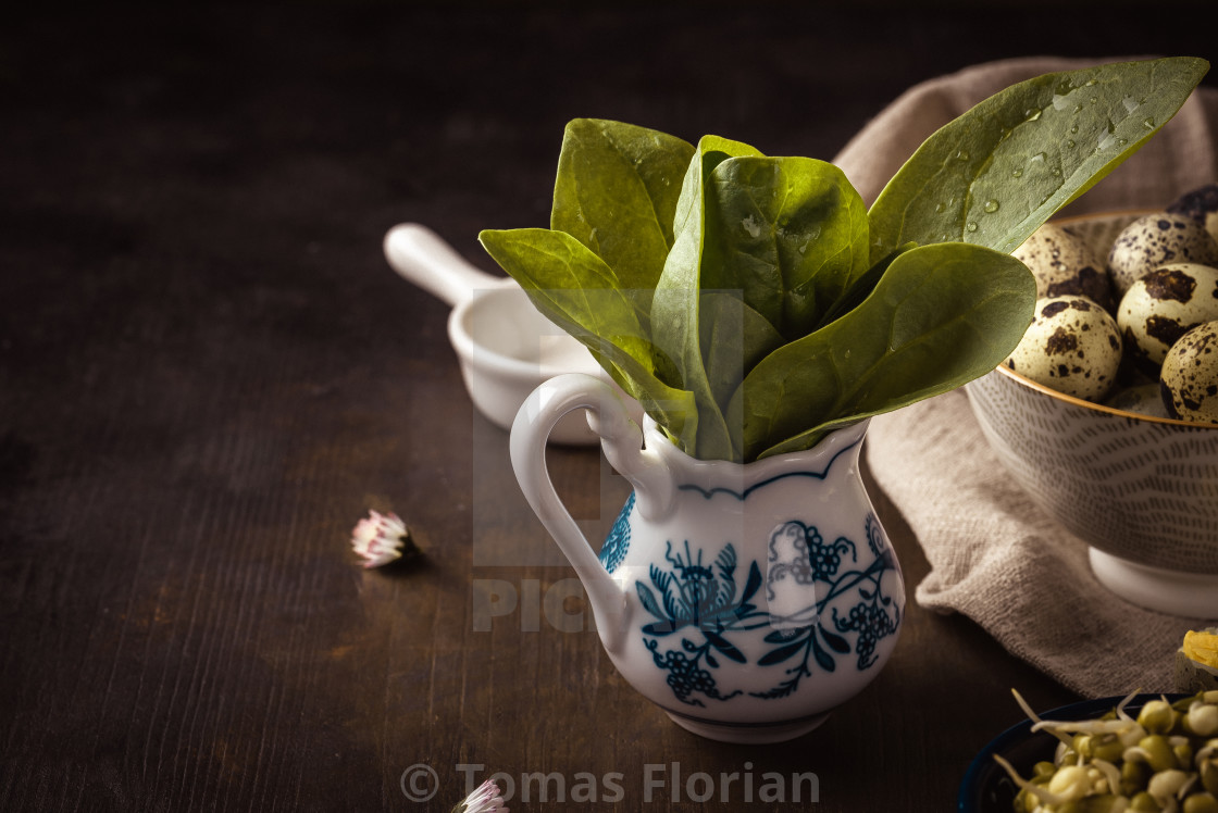 """Fresh green spinach leaves in ceramic bowl on wooden board"" stock image"