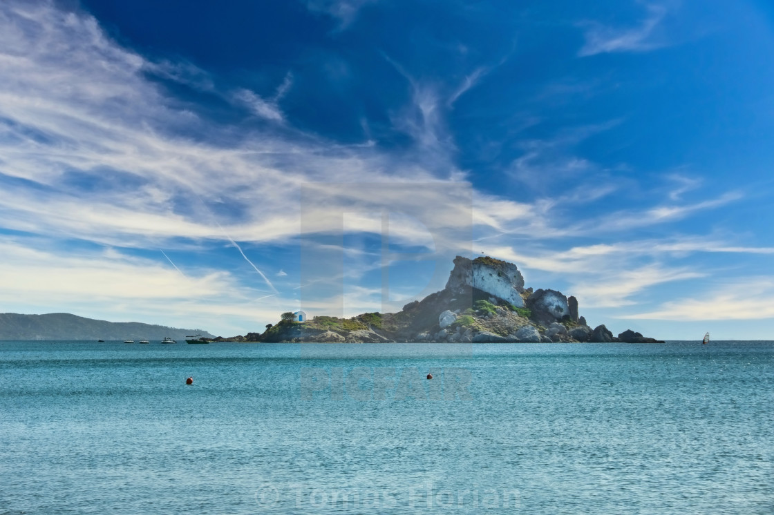 """View from beach on Kos island to small rock with church"" stock image"