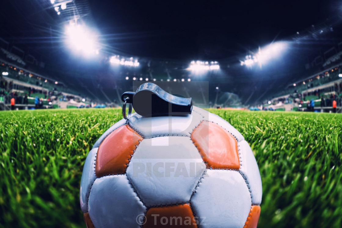 Football ball with whistle on the grass on soccer stadium ...