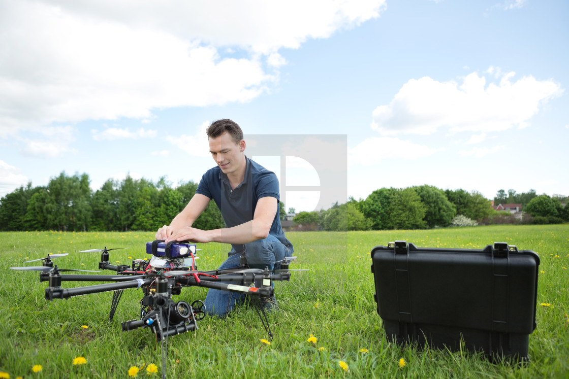 """Engineer Fixing UAV Drone in Park"" stock image"