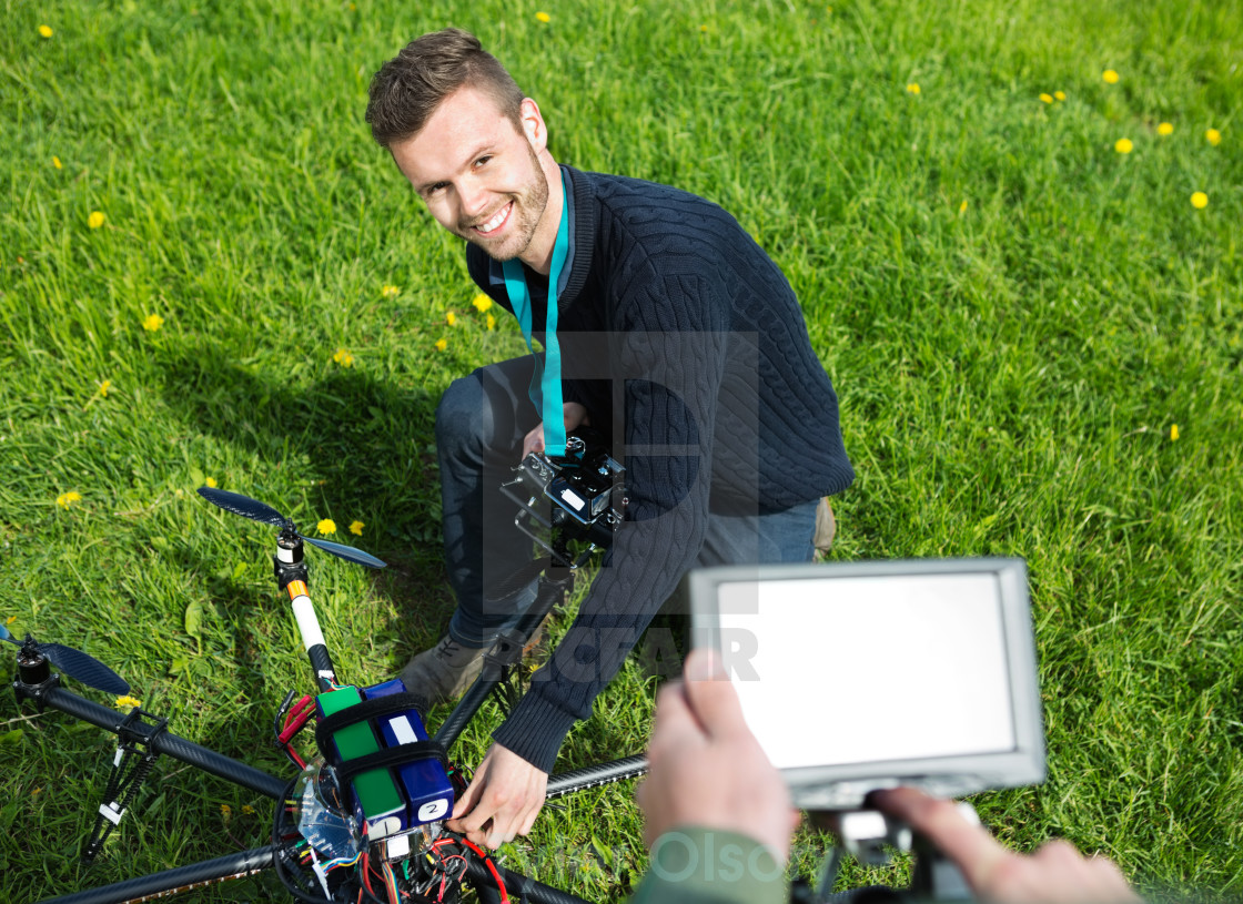 """Engineer Fixing UAV Helicopter in Park"" stock image"