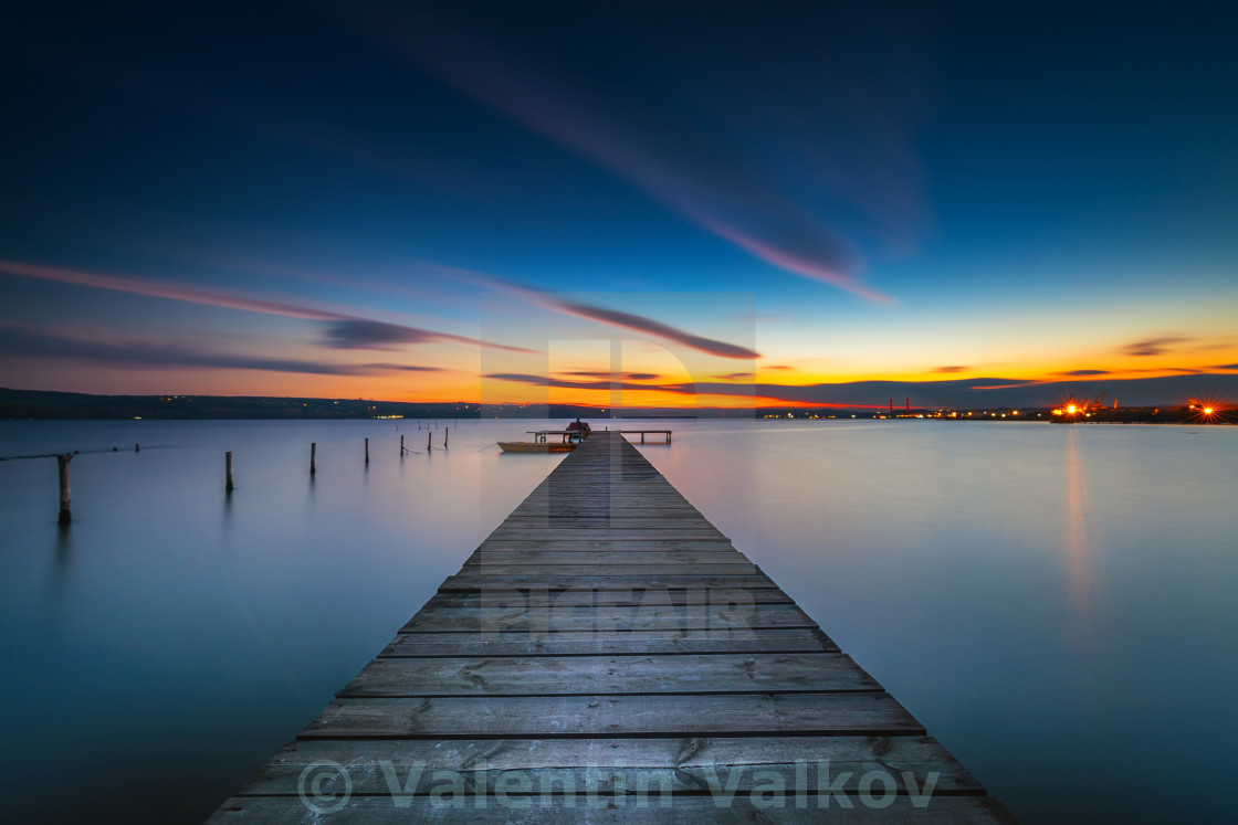 """Wooden Dock and fishing boat at the lake, sunset shot"" stock image"