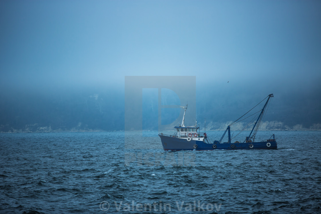 """""""Trawler fishing boat sailing in open waters on a cold and foggy"""" stock image"""