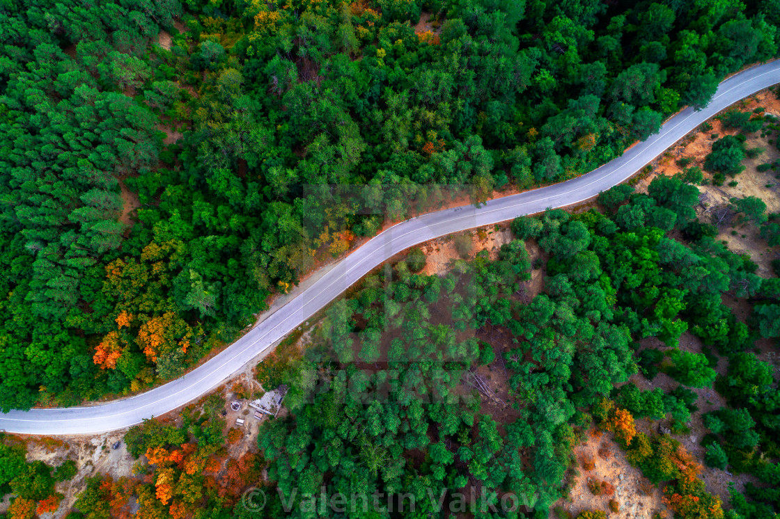 """Aerial view of drone over mountain road going through forest lan"" stock image"