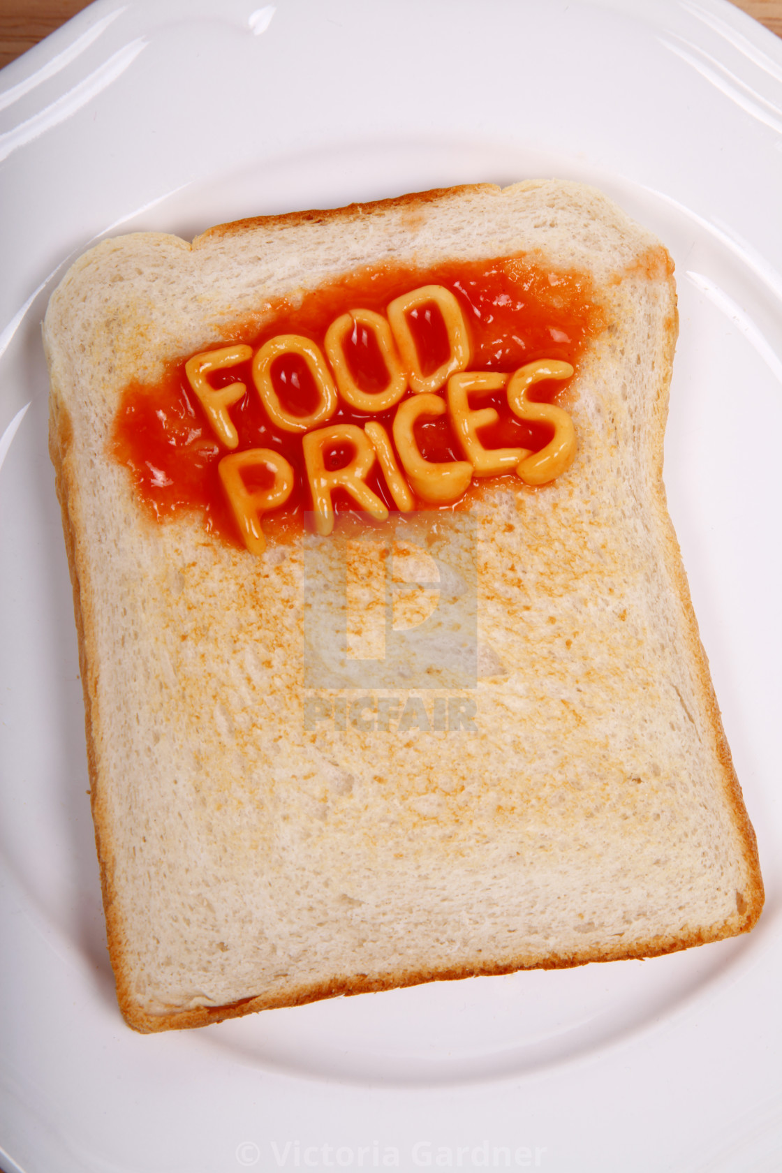 """A slice of toast on a plate with the word food prices spelled out in alphabet spaghetti"" stock image"