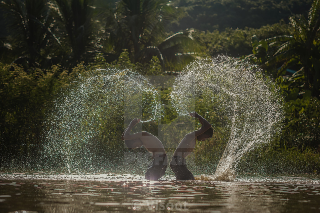 """Children playing splashing water in the river."" stock image"