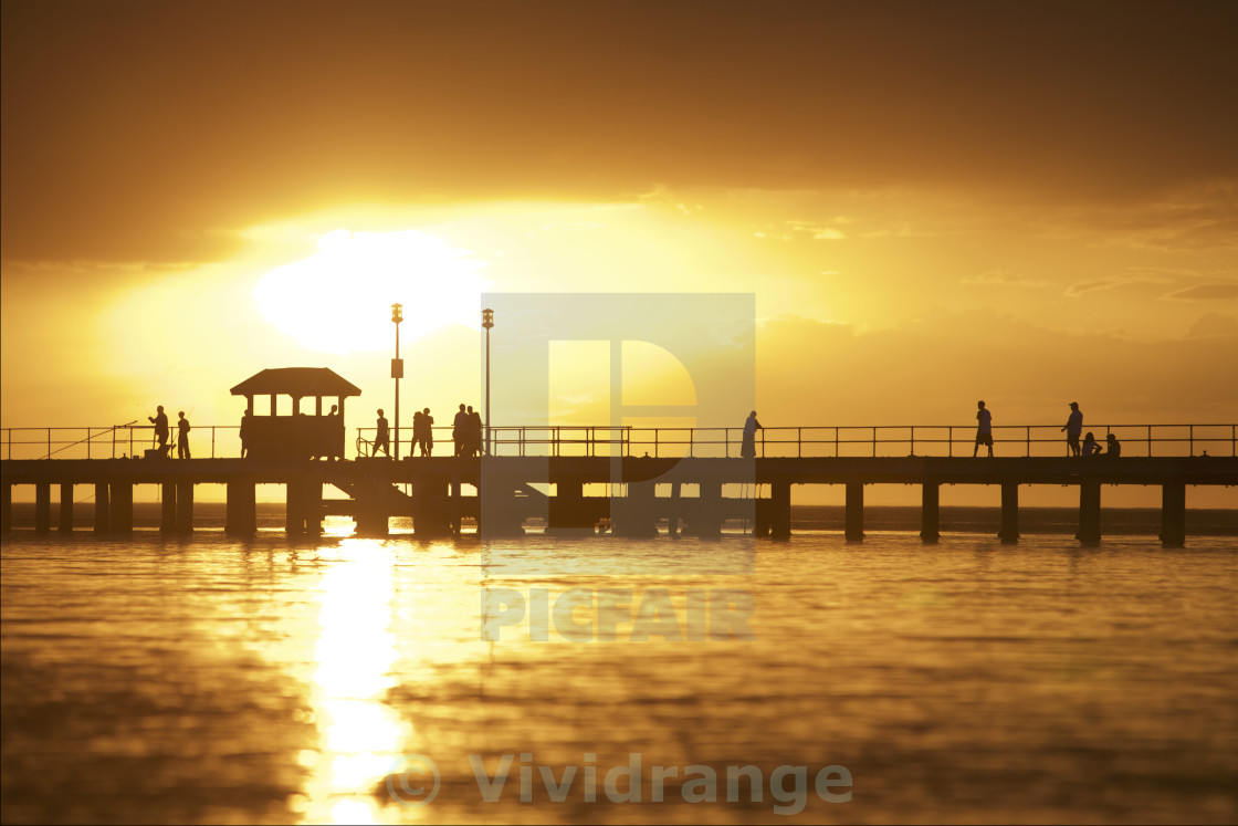 """Sunset setting over pier"" stock image"