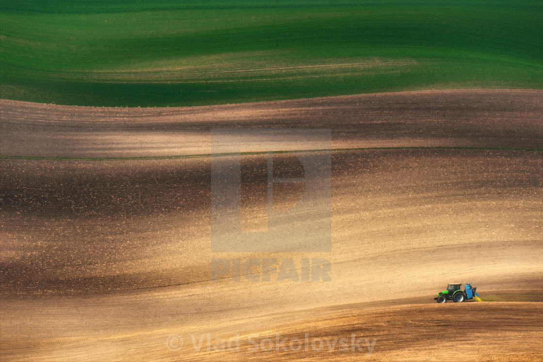 """FIELD RUNNER. Farming tractor plowing and spraying on field."" stock image"