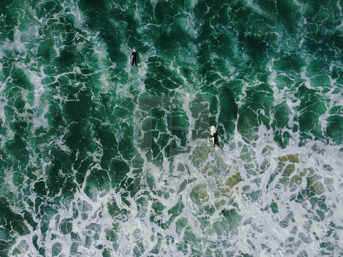 Looking down on a a surfing paddling out in cold waters - License