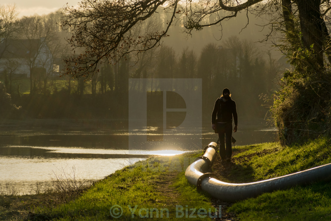 """Man Walking By The River"" stock image"