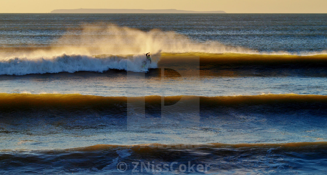 """""""Riding the waves at sunset"""" stock image"""