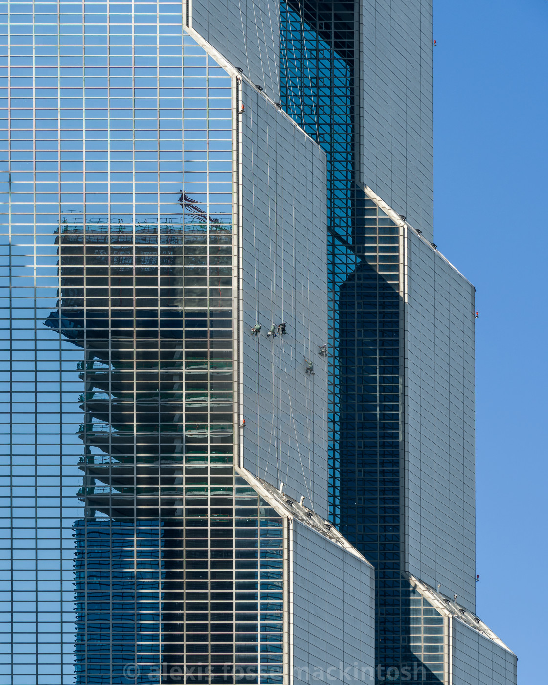 """Climbers: Window washers scale a highrise in Seoul South Korea to clean the grime from the windows of an office tower"" stock image"