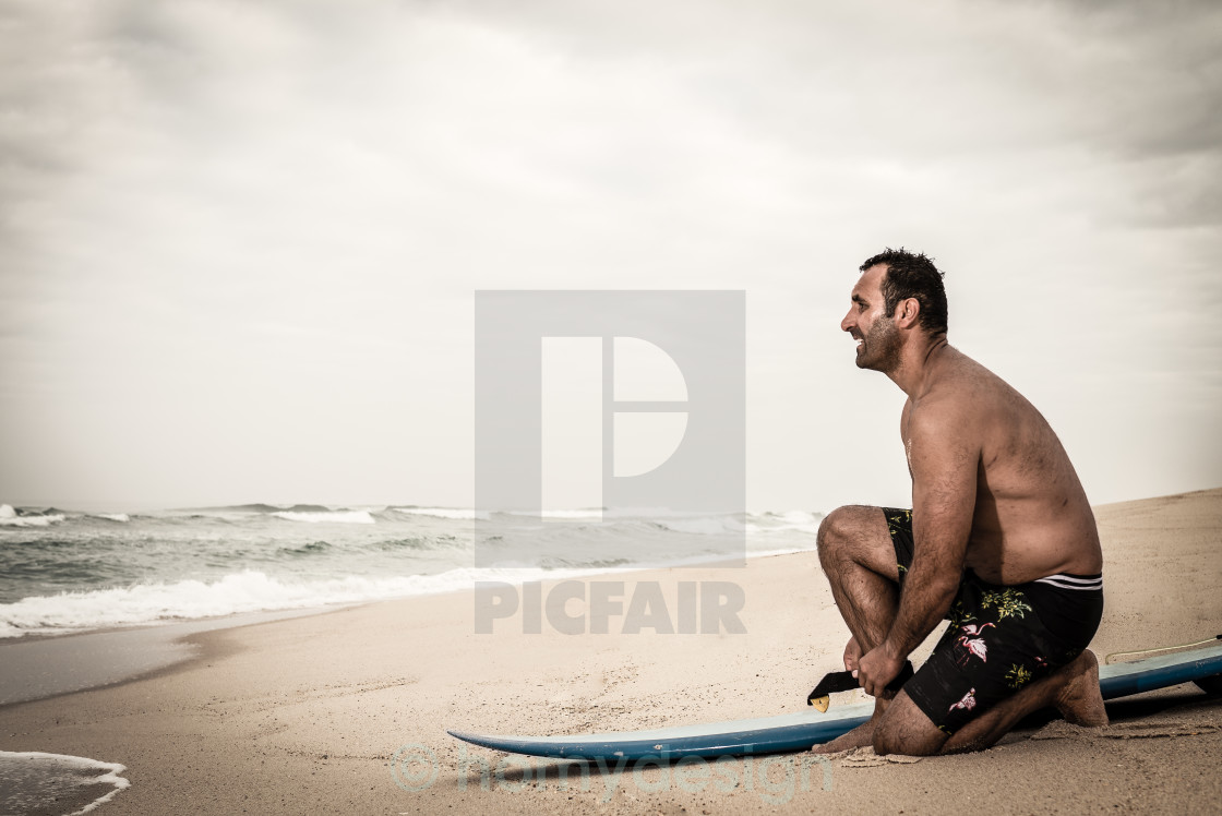 """Surfer tying his surfboard's leach"" stock image"