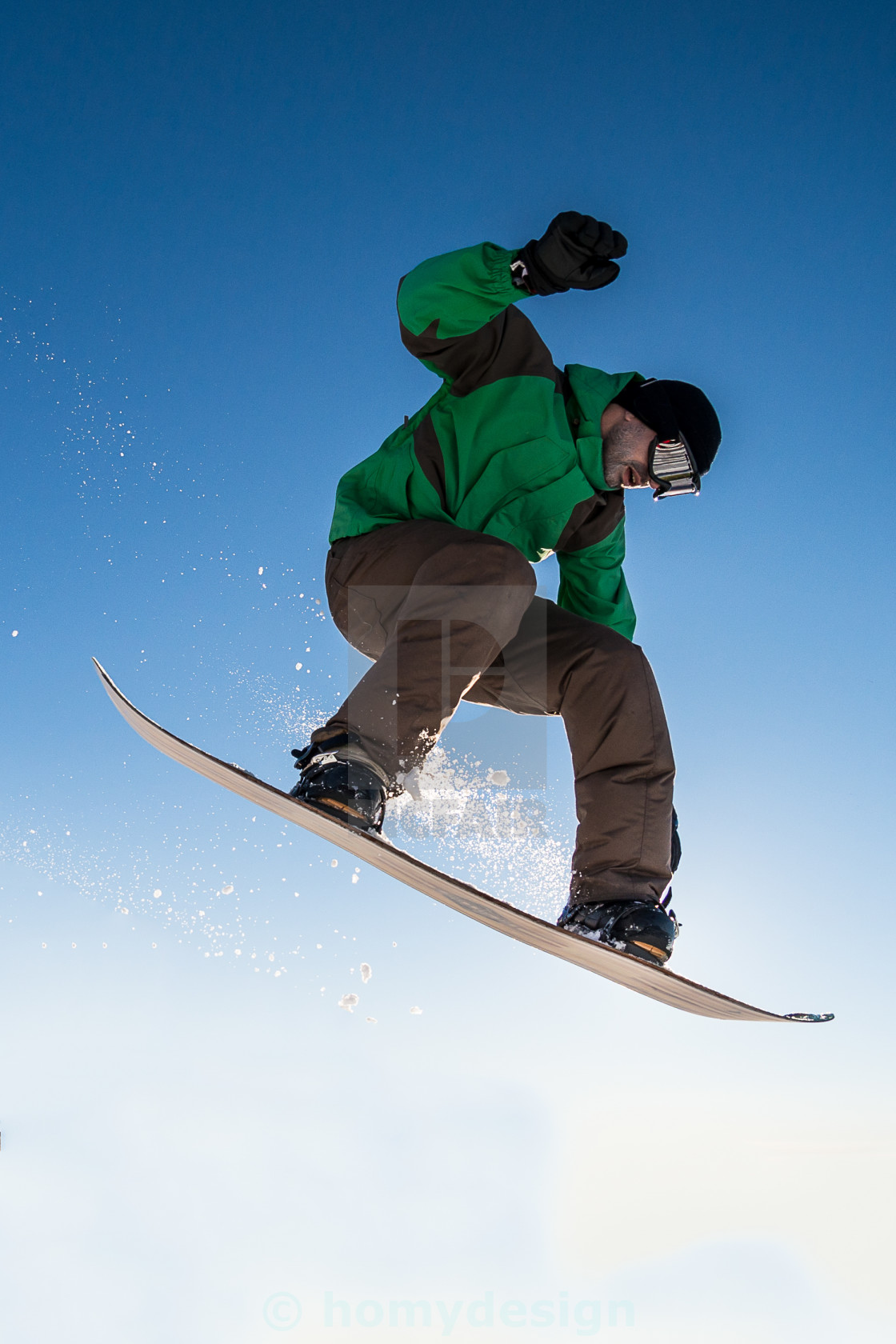 """Snowboarder jumping against blue sky"" stock image"