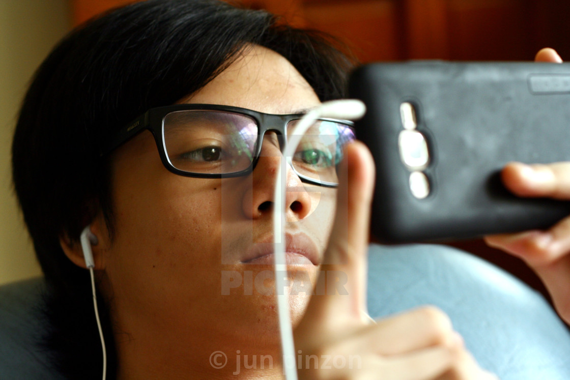 """""""Teenager with eyeglasses using a smartphone"""" stock image"""