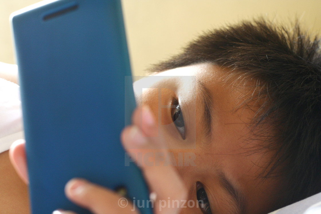 """Young kid watching on a smartphone"" stock image"