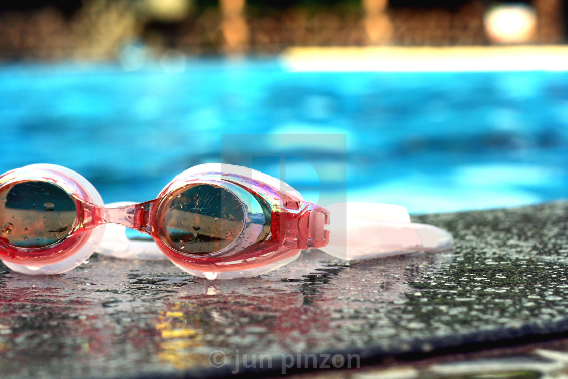 """""""Pair of swimming goggles beside a swimming pool"""" stock image"""